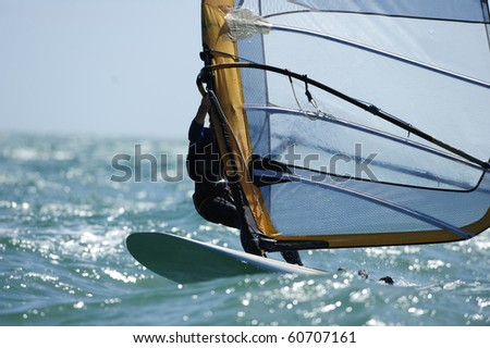 A sailboarder glides across the ocean water. - stock photo