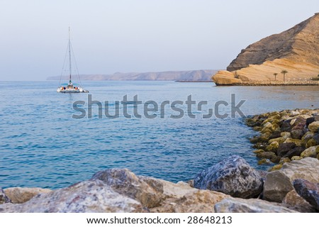 A sailboat anchored in a secluded bay next to the beach.