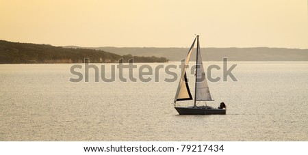 A sailboat basked in golden light on Lewis and Clark Lake in South Dakota.