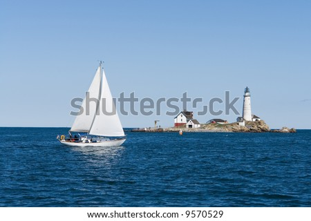 A sailboat crosses in front of Boston Light - stock photo