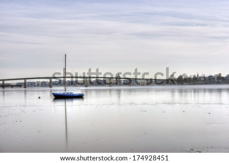 A sailboat frozen on an icy Severn River in Annapolis with US Naval Academy in background - stock photo