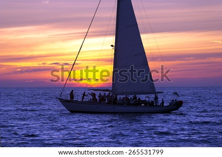 A Sailboat full of party people on vacation sails along the ocean as the sun sets in the background - stock photo