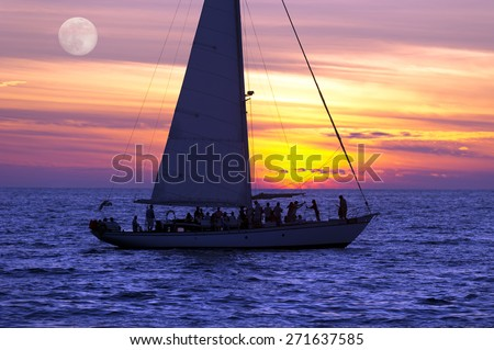 A sailboat full of people sails along the ocean at sunset as the moon rises in the background. - stock photo