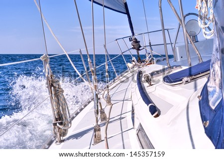 A sailboat heading into the open ocean under starboard tack and a reefed headsail. - stock photo
