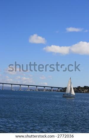 A sailboat in San Diego Harbour.  Coronado Bridge in the background. - stock photo