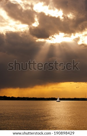 A sailboat on the Chesapeake Bay at sunset with a stormy sky - stock photo
