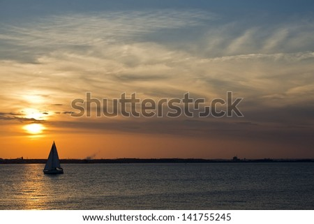 A sailboat on the Chesapeake bay in Maryland at sunset - stock photo