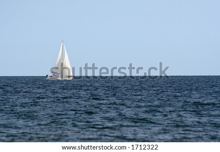 A sailboat sailing on the open sea against the blue sky,