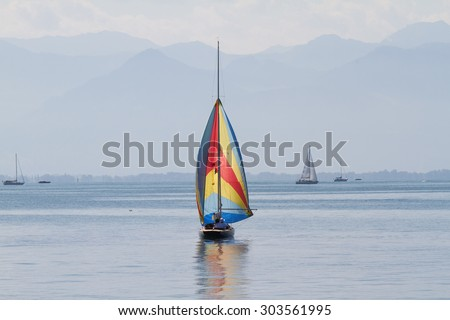 A sailboat with colorful sails moves over Lake Constance.