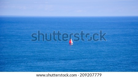 A sailboat with red and white sails in the calm sea. (Brittany, France) Dreams come true concept. - stock photo