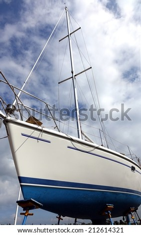 A sailing yacht is placed on a scaffold for repair and maintenance - stock photo