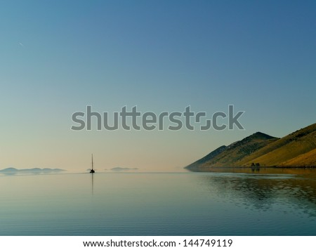 A sailing yacht leaving the Statival bay of the island Kornat in the Adriatic sea of Croatia - stock photo
