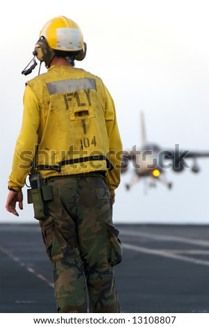A sailor watches as a naval aircraft lands aboard an aircraft carrier