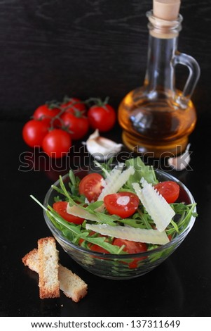 a salad of arugula, tomatoes and parmesan
