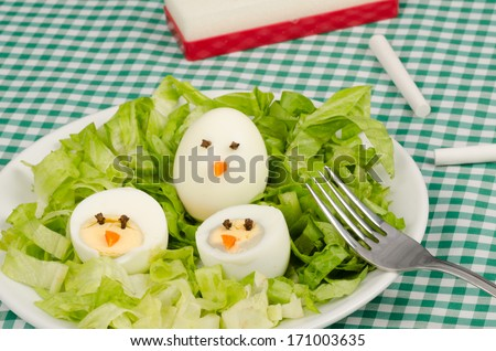 A salad served with decorated eggs, a kid meal - stock photo