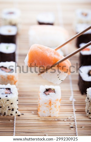 a salmon nigiri sushi being picked up with chopsticks with different types of maki sushi pieces on a wooden sushi mat in the background - stock photo