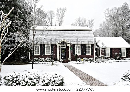 A salt box style home covered with fresh snow. - stock photo
