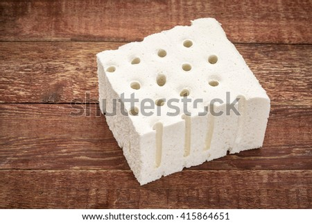 a sample of natural latex used in organic mattresses over rustic barn wood - stock photo
