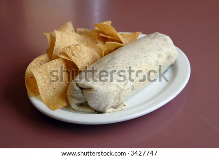 A San Francisco style Burrito served on a plate with tortilla chips on a dark red tabletop - stock photo