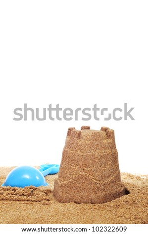 a sandcastle and a toy shovel on the sand on a white background - stock photo
