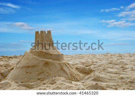 A sandcastle on a sandy beach, set against a bright blue summer sky. - stock photo