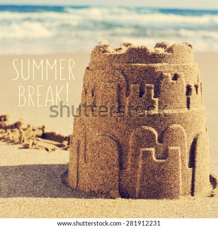 a sandcastle on the sand of a beach and the text summer break - stock photo