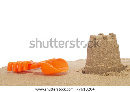 a sandcastle with shovel and rake on a white background - stock photo