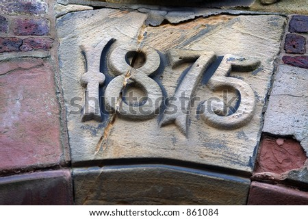 A sandstone key-stone in a building arch showing the construction date of 1875.