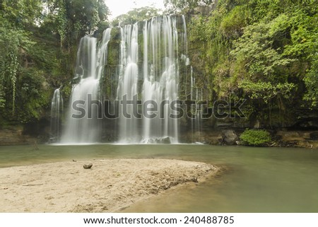 A sandy beach at a popular swimming hole at Llanos de Cortes  waterfall near Bagaces, Costa Rica