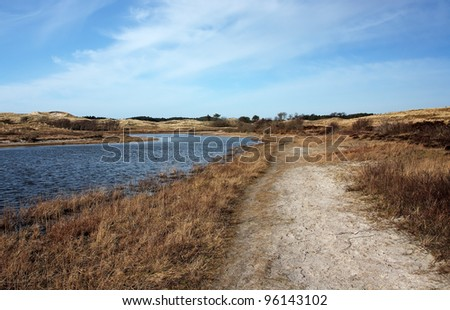 A sandy path in the dunes near the Dutch coast, with a lake. - stock photo