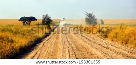 a sandy road through a beautiful african landscape - stock photo