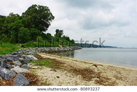 A sandy rock lined Beach of the York river in Yorktown Virgina on an overcast summer day looking up river to the Naval Weapons Station with room for your text. - stock photo