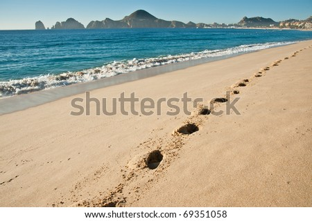A sandy tropical beach with foot prints - stock photo