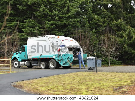 A Sanitation Worker dumps a trash can into a garbage truck.