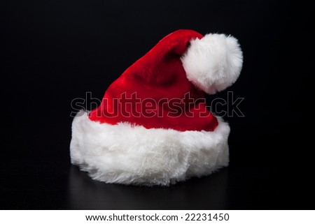 A Santa Clause hat on black background. - stock photo