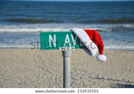 A santa hat on a street sign at the ocean during the fall. - stock photo
