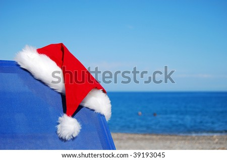 A santa hat resting on a sun lounger by an exotic beach to give a christmas vacation concept. - stock photo