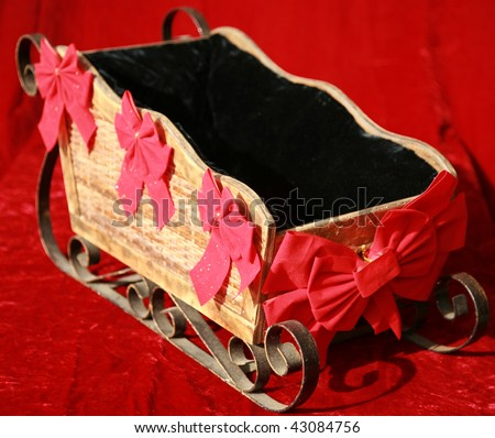 a santa sled with red bows on a red velvet background - stock photo