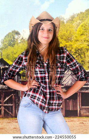 A sassy young teen cowgirl in an old western town. - stock photo