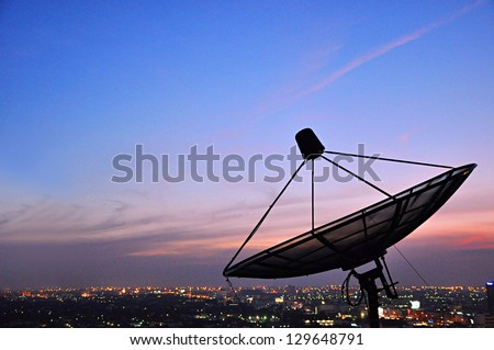 A satellite dish above the city - stock photo