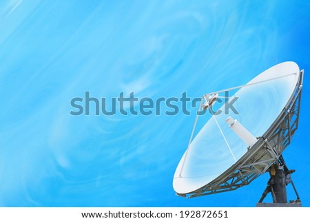 A satellite dish in a field of tree under blue sky. - stock photo