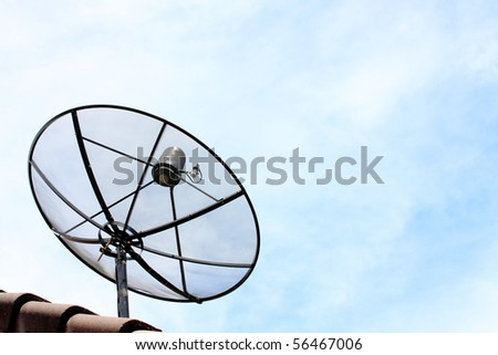 A satellite dish on the roof with blue cloud sky.