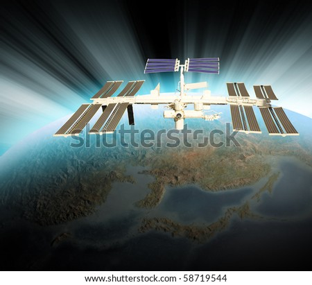 A satellite is above the Earth and is orbiting the planet. There is a white blue glow from the sun on the horizon. Use it for a space or technology theme. - stock photo