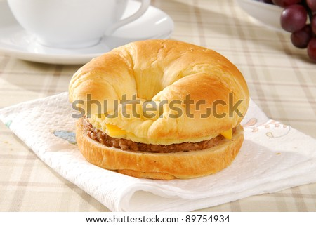 A sausage and egg croissant with coffee - stock photo