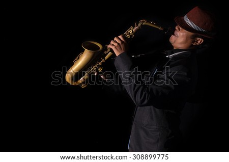 A saxophone player in a dark background, black and white tone - stock photo