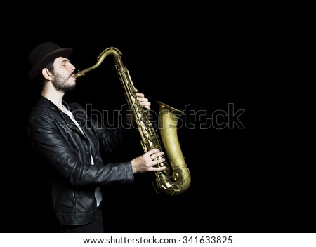 A saxophone player in a hat. dark background.  Saxophonist jazz man with Sax. Leather Jacket dressed saxophone player in a dark club setting - stock photo