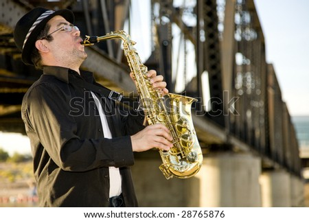 A saxophonist plays outdoors against an  industrial backdrop. - stock photo
