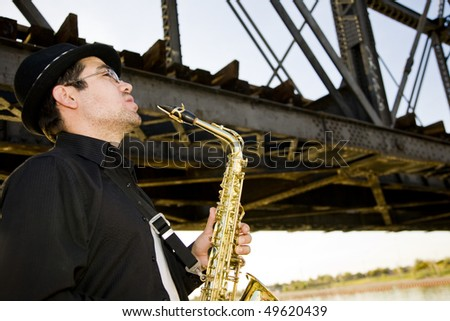 A saxophonist plays outdoors at sunset against a grungy industrial skyline.