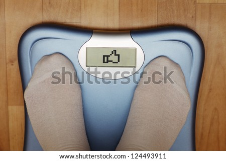 "A scale with two feet of the person standing on it on a wooden floor. The scale says: ""LIKE"". - stock photo"