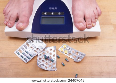 A scale with two feet of the person standing on it - on a wooden floor with pills to loose weight. The scale display is empty - copyspace. - stock photo